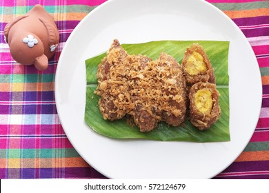 Thai dessert recipes, Khao mao tod,  battered and deep fried unripe rice and grated coconut banana rolls. Place on green leaf and white plate.