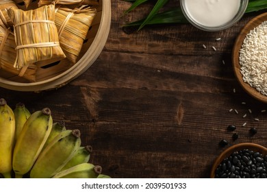 Thai Dessert, Steamed sticky rice with banana and black beans wrapped in Nipa palm leaves on a wood background. The main ingredients are Sticky Rice, Banana, Black Beans, and Coconut Milk.