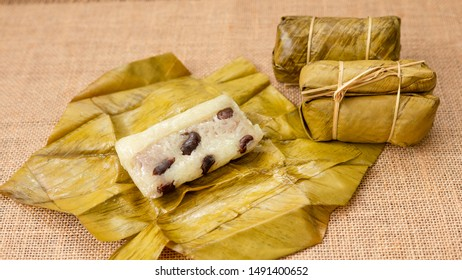 Thai dessert sticky rice or Khao Tom Mad, Wrapped the banana in sweet sticky rice on a banana leaf with sackcloth background.