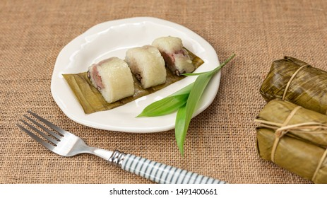 Thai dessert sticky rice or Khao Tom Mad, Wrapped the banana in sweet sticky rice on the white plate with sackcloth background.