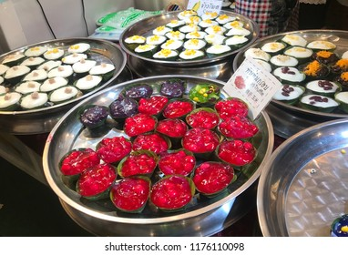 Thai desserts come in a variety of colors, placed in a tray and on a variety of shelves.