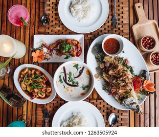 Thai dinner food with rice, Stir fried calamari and shrimp, Chicken soup with coconut milk, chicken grilled BBQ sauce, fried barramundi fishwith herb on the white plate over wooden table in restaurant