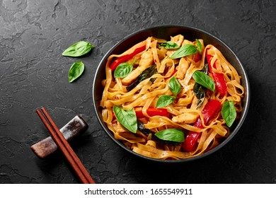 Thai Drunken Noodles or Pad Kee Mao in black bowl at dark slate background. Drunken Noodles is thai cuisine dish with Rice Noodles, Chicken meat, Basil, sauces and vegetables. Thai Food. Copy space