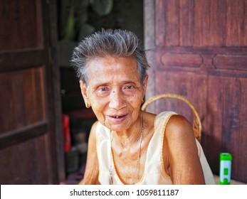 Thai elderly is sitting and smiling happily on the chair at her home in the countryside of Thailand, Happy Asian older people in the rural of asia, It represents a good physical and mental health.