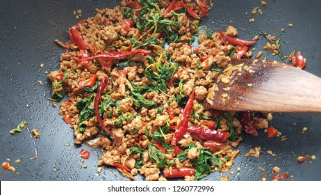 Thai famous spicy cuisine : Stir-fried minced pork with basil in the metal frying pan with Bamboo Stir Fry Spatula. Home cooking concept - top view