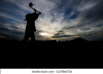 Thai farmer and he is carrying a hoe or weed tool at twilight time on rice field. Picture is silhouette style.