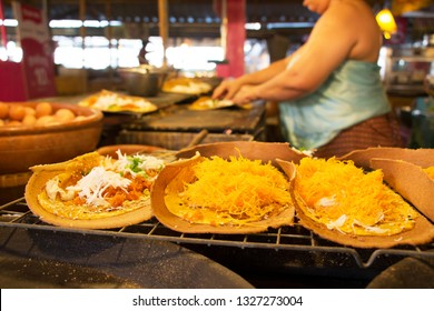 Thai female sellers make some large crispy pancake fillings with sweet egg floss, and fillings salty coconut, minced shrimp at Khlong Lad Mayom Market,  Taling Chan District, Bangkok, Thailand.