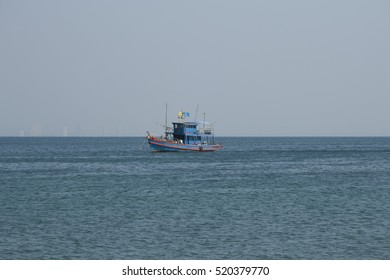 Thai fish boat in the sea with skyscrapers of Pattaya as a background