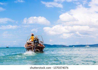 Thai fisherman sailing in the sea on a long-tail boat. To fish. On the background of the yacht and cruise liner. Coast province Krabi, sunny day.