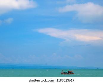 A Thai fishing boat chugs along an aqua-green ocean under a big, blue sky near Koh Chang island in Thailand