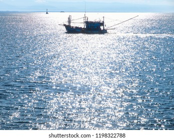 A Thai fishing boat silhouetted on a sparkling ocean in early morning near Koh Chang island