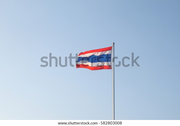 Thai flag on blue sky background have red, white and blue color