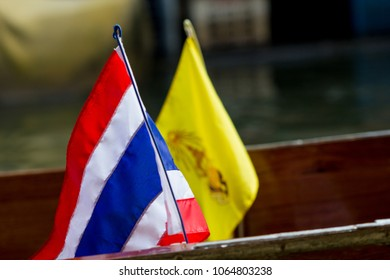 Thai flag and the Royal flag of Thailand on a wooden boat