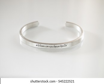 """Thai Font Laser Engraving """"To commemorate the royal of the 9th king of Thailand"""" on a ring on white background"""