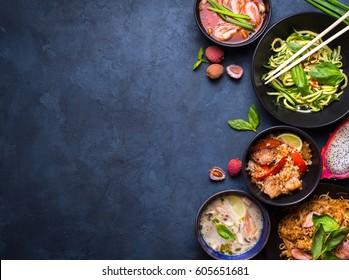 Thai food background. Dishes of thai cuisine. Tom yum, tom kha gai, pad thai noodles, fried rice with pork and vegetables khao phat mu, green papaya salad som tam, thai fruits. Space for text
