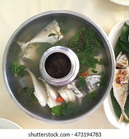 Thai food clear spicy hot & sour soup (Tomyum) with boiled asian red tail cat fish fillet and herb