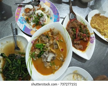 Thai food dinner background, fish tomyam, omelet, Red Curry, salted egg, ipomoea, stainless steel dining table, a spoon