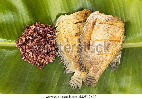 thai food fried fish Trichogaster pectoralis, salid fish (thai name) with thai brown rice on banana leaf