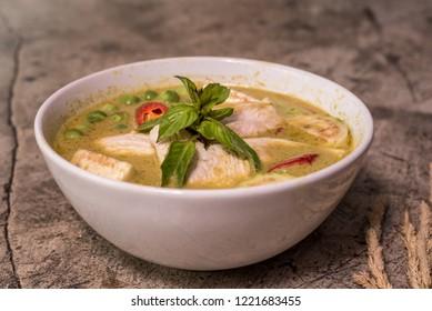 Thai food green curry chicken in dish wood dark background