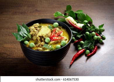 Thai food, green curry chicken with coconut curry on a wooden table.
