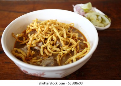thai food Khao soy a famous northern noodle dish in beef curry with wood background