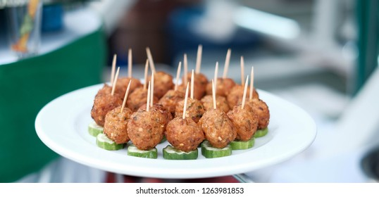 Thai food is minced pork ball mixed with spicy spices. Make a dough and fry it in a white plate on the table.