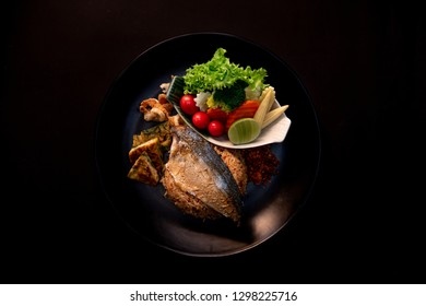 Thai Food Recipe.Fried rice with fried mackerel paste On a black plate  . Thai Food Recipe.Fried rice with fried mackerel paste  On a black background