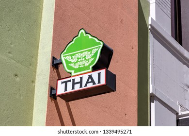 Thai food restaurant sign mounted on building wall