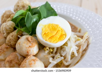 Thai Food. Rice Noodles in Fish Curry With boiled egg, fish balls, pork snack, basil, bean sprouts on top, placed on a wooden table.