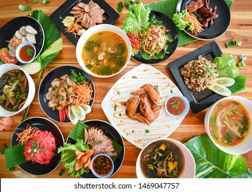 Thai food served on dining table / Tradition northeast food Isaan delicious on plate with fresh vegetables - Many variety various Thai menu Asian food on a wooden table , top view