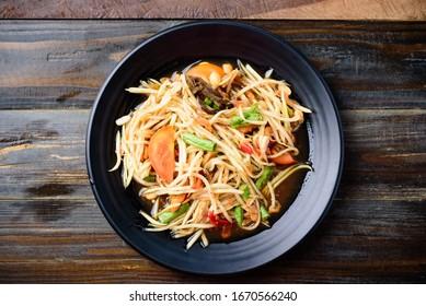Thai food (Som Tum), spicy green papaya salad on wooden background, top view