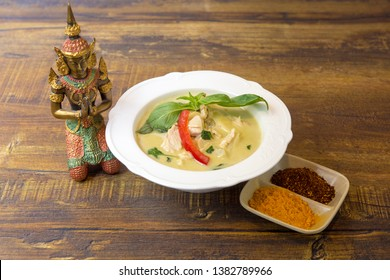 Thai food speciality. Kang Kiew Wan Kai: curry thai soup with chicken and sweet pepper. Served with Thaï decoration on a wood table.