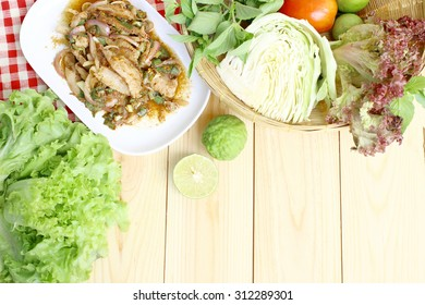 Thai food, spicy grill pork with chili and vegetables on wood background with space for text