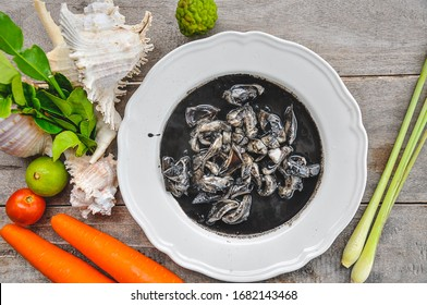 Thai food, Squid in black ink sauce - The best Thai seafood dishes in Bangkok Thailand,  with squid ink, pepper, garlic, lemon in a white plate on a wood background. Top view.