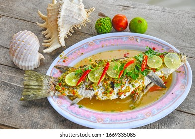 Thai food, Steamed Fish in Lemon Sauce with fragrant ingredients as fresh lime juice, garlic, and chilies. and being sour, spicy, garlicky. This is excitement of flavors in Thai Seafood. top view - Shutterstock ID 1669335085