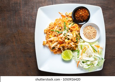 "Thai food, Stir fried noodles from Thailand call ""Pad Thai"" served with cayenne pepper, lemon sliced, groundnut in white plate on wooden table."