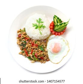 Thai food stir-fried pork spicy and basil served with rice and fried egg and tomato cucumber carved  white plate  top view isolated on white background
