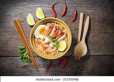 Thai food style noodle, tom yum kung on wood background