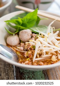 Thai food - Thai style spicy Tomyam noodle soup, famous Thai noodle soup on wooden table, selective focus.