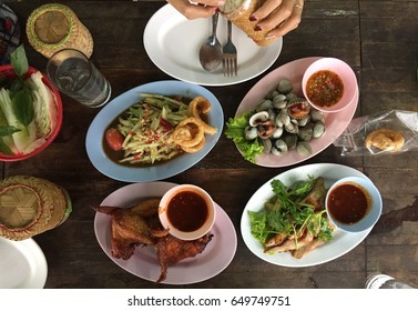 """Thai food style:""""Isan food""""papaya salad,grilled pork with many other thai eastern food on wooden table"""