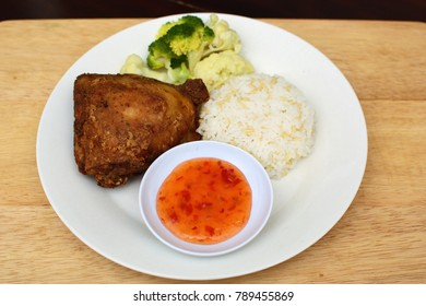 Thai fried chicken with pepper serve with rice, vegetables and chili sauce on the white plate