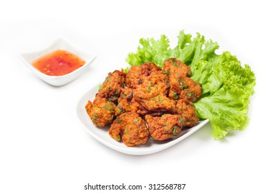 Thai fried fish cake (Tod Mun Pla) or prawn fritter ball serve with red sauce Thai  traditional food recipe isolated on white background