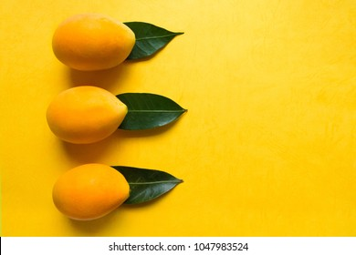 Thai fruit scene. Gandaria fruit (Mayongchid Maprang Marian Plum and Plum Mango) decoration with leaves on a yellow background.