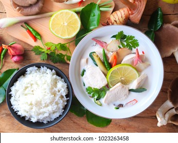 Thai galangal chicken soup in creamy  coconut milk or Tom Kha Gai, famous traditional Thai food serve with jasmine steam rice in top view on wooden table background with ingredients.