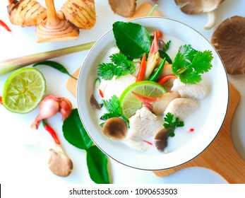 Thai galangal chicken soup in creamy  coconut milk or Tom Kha Gai,famous traditional Thai food on white background in top view with ingredients.