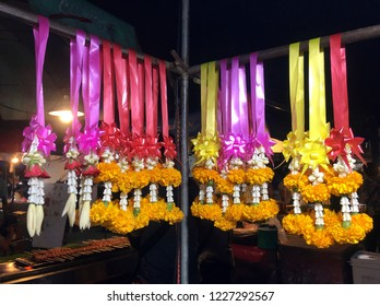 Thai garland with colorful ribbon on the rack at night market. It is used for worship Bhudda.