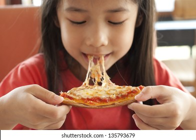 Thai girl enjoy eating pizza.