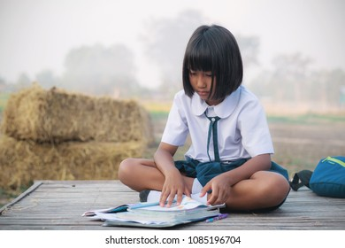 Thai girl sitting reads a book on bamboo mat in the countryside.