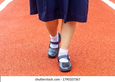 Thai girl student in uniform shoes walking on red cement road with dried leaf