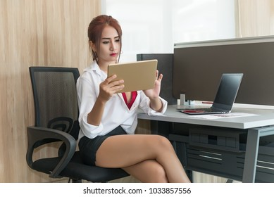 Thai girl work on the desk,business woman use tablet for looking stock market,Secretary working concept